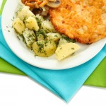 Roast chicken cutlet with boiled potatoes on plate, isolated on